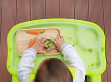 Top View Of Infant Baby Eating By Baby Led Weaning (BLW). Finger Foods Concept.