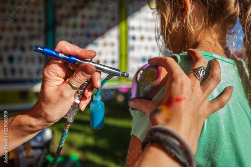 Photo Young girl getting an airbrush stencil temporary tattoo in a family festival out