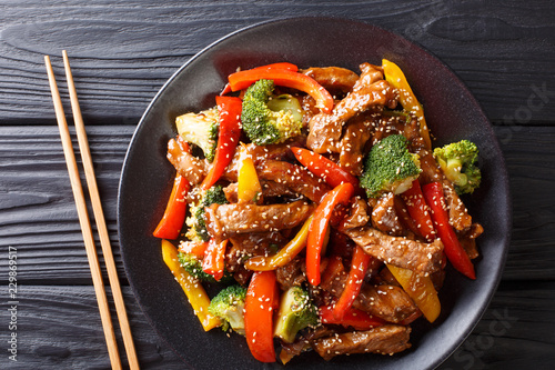 Stir-fried teriyaki beef with red and yellow bell pepper, broccoli and sesame seeds close-up on the table. horizontal top view