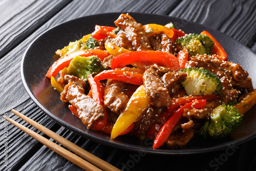 Spicy teriyaki beef with red and yellow bell peppers, broccoli and sesame seeds close-up. Asian style. horizontal