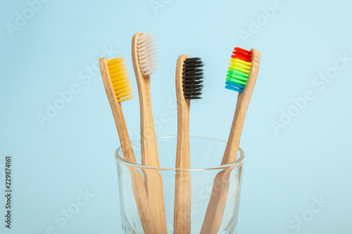 Stickers pour porte Pierre, Sable Set of toothbrushes in glass on blue background. Concept toothbrush selection, bamboo eco-friendly. Concept of sexual minorities and LGBT community