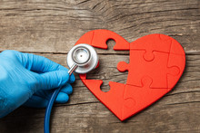 Heart Puzzle Red And Stethoscope On Wooden Background. Concept Diagnosis And Treatment Of Heart Disease, Medical Insurance