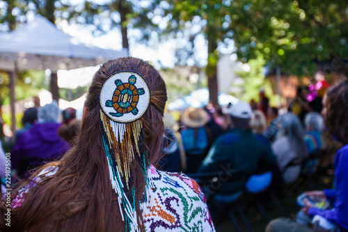 Woman is wearing a large turtle beaded hair pin and colorful native clothing while listening to a concert as part of a native arts festival