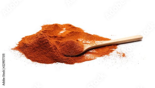 Pile of red pepper, paprika powder with wooden spoon isolated on white background