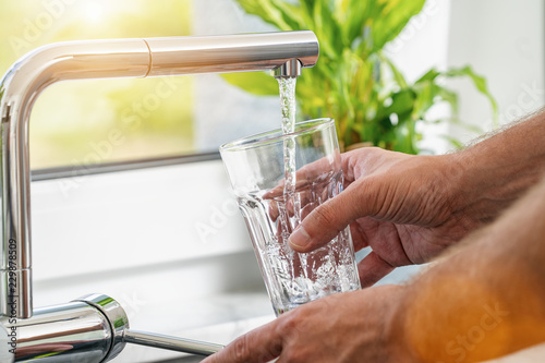 Fototapety, obrazy: Closeup shot of a man pouring a glass of fresh water from a kitchen faucet