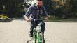 Playful man wearing jeans and plaid shirt riding a green bicycle for children in park. Joyful dad remember childhood. Summertime. Outdoors.