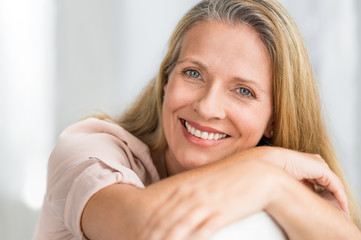 Fototapeta Smiling mature woman on couch