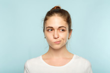 Puzzled Skeptic Doubtful Young Beautiful Woman With A Hair Bun On Blue Background. Emotional Facial Expression.
