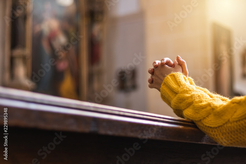 Obraz Christian woman is praying with hands crossed in church  - fototapety do salonu
