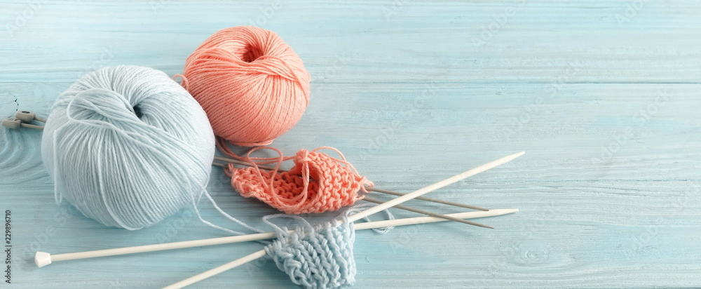 Fototapety, obrazy: Knitting wool and knitting needles in pastel blue and pink colors on blue  wooden background. top view.copy space.banner