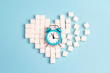 Broken Heart Made Of Sugar Cubes With Alarm Clock On A Blue Background.