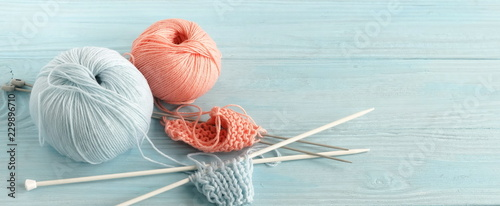 Photo  Knitting wool and knitting needles in pastel blue and pink colors on blue  wooden background
