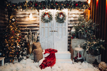 Front View Of Stylish Decorated Studio For Christmas Holiday, With Big White Doors In Center Of Wall. Exterior Of House Preparing For X Mas. Christmas Tree, Many Presents And Pine.