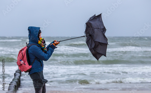 Foto strong wind destroys a woman's umbrella during a beach walk