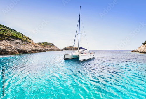 Canvas Beautiful bay with sailing boat catamaran, Corsica island, France