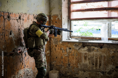 Cuadros en Lienzo  sniper with automatic rifle by the window in building