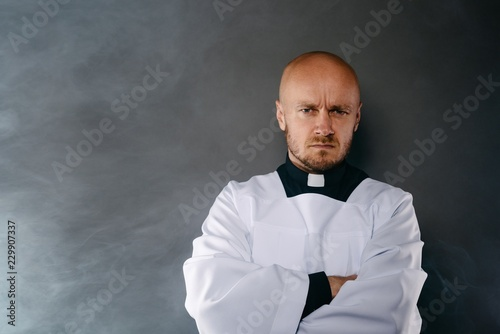 Obraz na plátně Priest in white surplice and black shirt with cleric collar