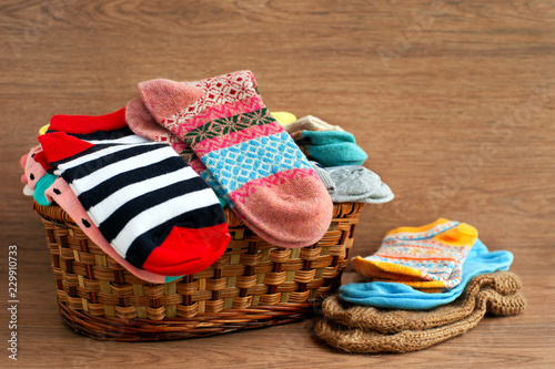 Basket with different socks. Socks of different sizes in a large wicker basket. Clothing for autumn and winter in the form of socks. A pile of colorful socks on a wooden background.
