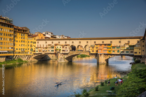 Foto op Aluminium Florence Yoga on the banks of the river Arno, while a kayak paddles under the Ponte Vecchio in Florence