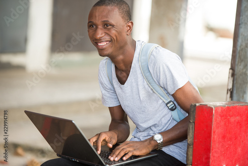 Fotografie, Obraz  young student man sitting in city working with laptop