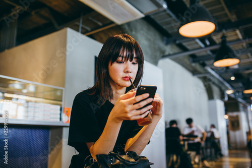 カフェでスマートフォンを使う女性
