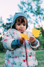 Girl Holding Yellow Autumn Leaves In Park