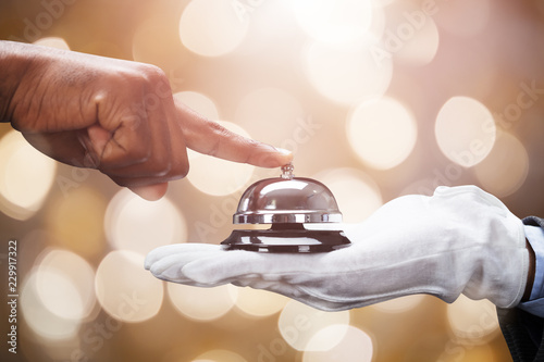 Customer Ringing Service Bell Held By Butler