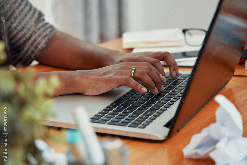Fototapeta Faceless shot of modern black businesswoman working on laptop and typing on keyboard at table in office