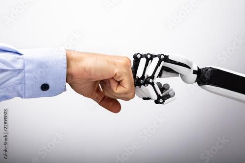 Photo Human Hand And Robot Making Fist Bump