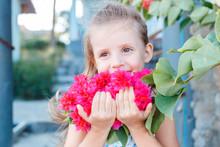 Little Girl Is Holding Beautiful Pink Flowers. Bougainvillea