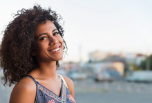 Black Woman With Curly Hair Flying In Wind Enjoying Evening