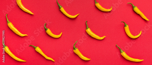 Hot yellow chilli peppers on red background