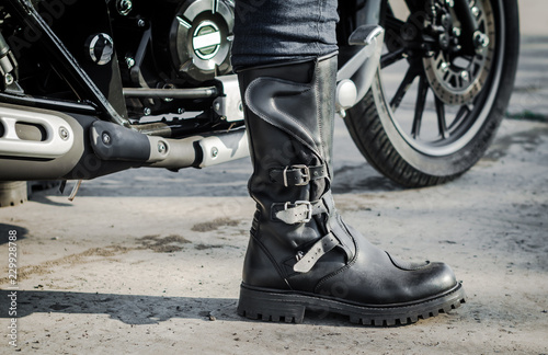 Fototapeta biker leg in a boot against the backdrop of a motorcycle obraz