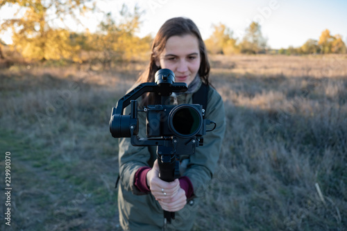 Tablou Canvas Female videographer holding a gimbal with mirrorless camera
