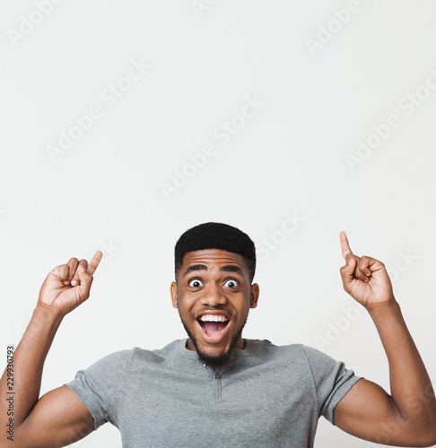 Fotografie, Obraz  Excited african-american man pointing upwards at copy space