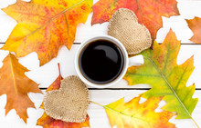 Cup Of Coffee With Two Burlap Hearts And Autumn Leaves On White Wooden Table.Top View.