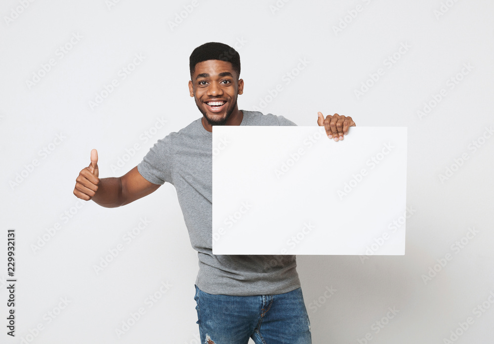 Fototapeta African-american man holding white blank board and showing thumb up