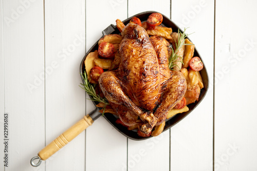 Fotografia Grilled whole chicken in cast iron black pan