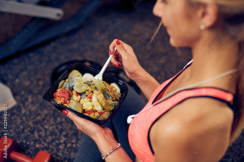 Fototapety, obrazy: Top view of woman eating healthy food while sitting in a gym. Heatlhy lifestyle concept.