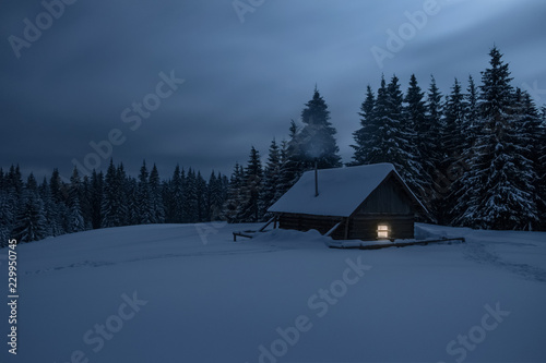 Wooden cabin under stars. Lights shines through the window from inside of the house. Night landscape in winter.