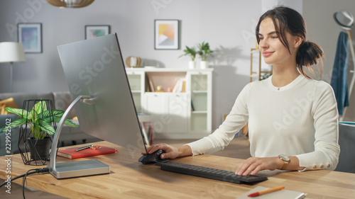 Portrait of the Beautiful Young Woman Working on Personal Computer from Her Cozy Living Room. She Smiles Charmingly.