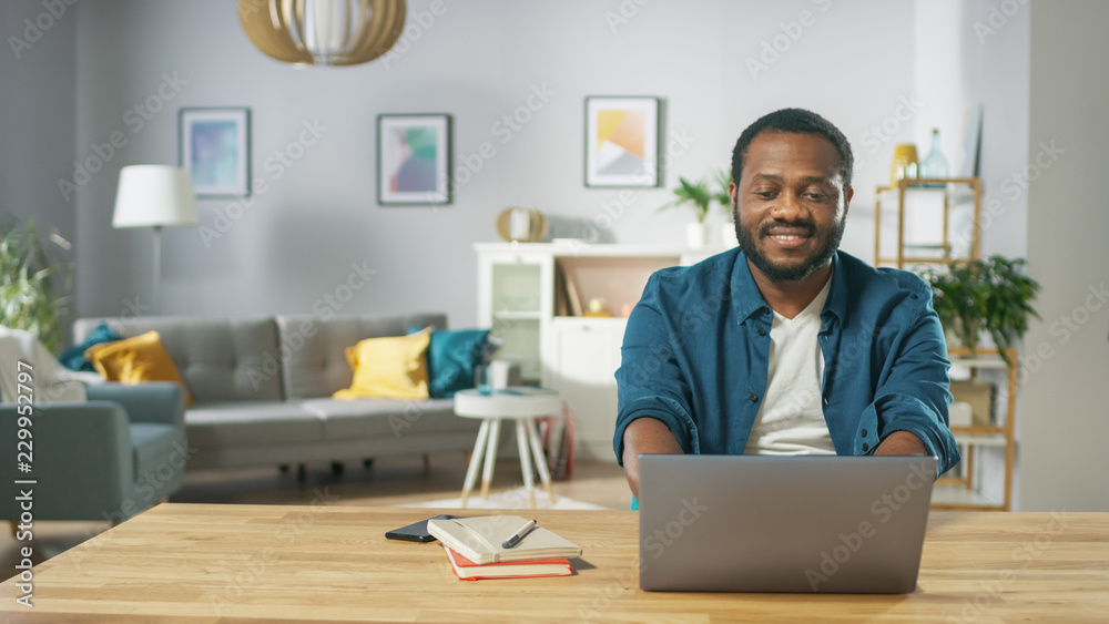 Fototapeta Portrait Shot of a Handsome Smiling Man Working on a Laptop at Her Desk in the Cozy Living Room.