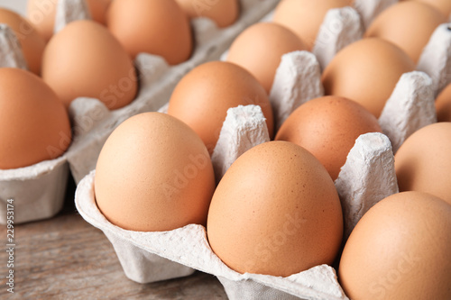Raw chicken eggs in carton, closeup view