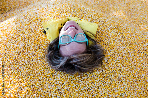 Fotografia, Obraz  An adult female has her entire body covered and buried in corn kernels in a corn