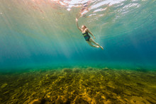 Young Woman Swimming Underwater In Crystal Clear Summer Lake