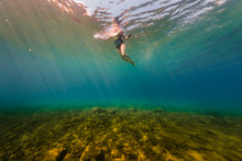 Woman Swimming Underwater In Clear Summer Lake