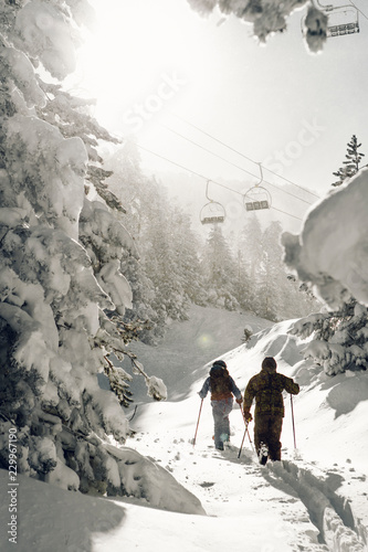 Two men walking in a snowy ski resort on a windy day