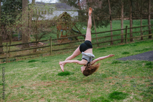 girl doing gymnastics in the back yard.