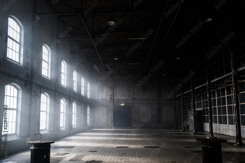 Fototapeta Sunlight shining throuh the windows of an old abandoned industrial warehouse building