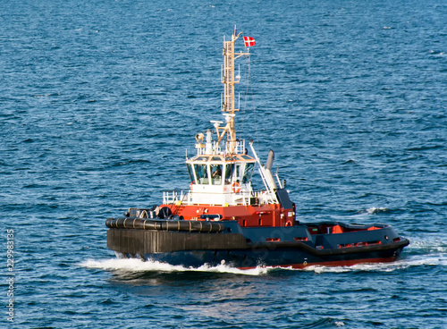 A tugboat with a Danish flag navigates on the sea